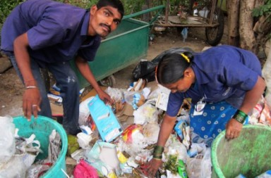 Swach Coop workers with uniform and id cards sort garbage